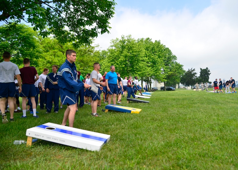 Members of Team Dover play cornhole during Wingman Day May 22, 2014, at the Eagles Nest Park on Dover Air Force Base, Del. The Eagles Nest Park hosted cornhole, horseshoes, volleyball and tug-o-war as team building events and a Wing for Wingman Day. (U.S. Air Force photo/Airman 1st Class William Johnson)