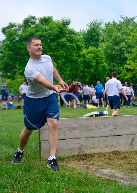 Staff Sgt. Caleb Dubourg, 436th Maintenance Squadron, throws a horseshoe during Wingman Day May 22, 2014, at the Eagles Nest Park on Dover Air Force Base, Del. Team Dover held a variety of team building events and sports to build morale and highlight all of the aspects of Airmen comprehensive fitness. (U.S. Air Force photo/Airman 1st Class William Johnson)