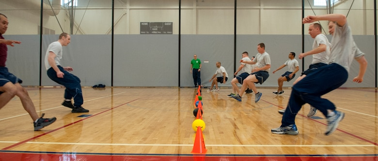 Team Dover Airmen run toward the center line to grab balls while playing dodgeball during Wingman Day May 22, 2014, in the fitness center on Dover Air Force Base, Del. Besides dodgeball, various sporting events took place across base. (U.S. Air Force photo/Airman 1st Class Zachary Cacicia)