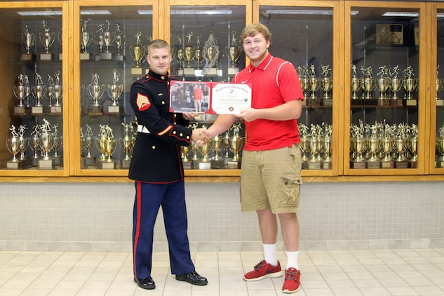 U.S. Marine Corps Sgt. Dennis Catrett, a Fredericksburg, Va. native and a recruiter with Recruiting Station Frederick, presents Steven Moss, an offensive guard for Chancellor High School's football team and a Semper Fi All-American Bowl competitor, with a certificate to recognize his participation in the bowl game during senior awards at the high school May 23, 2014. The SFAAB honored selected players who demonstrated the Marine Corps' commitment to developing quality citizens, and reinforced our core values of honor, courage, and commitment, on and off the field.   Like the Marine Corps, the Semper Fidelis Football Program demanded quality of character, excellence in education, and proven physical fitness. (U.S. Marine Corps photo by Capt. Herman Davis/Released)