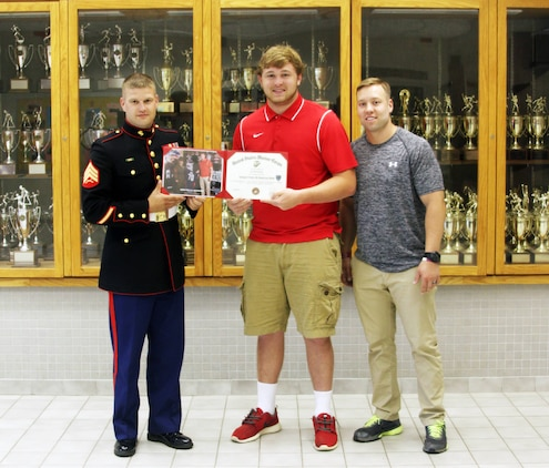 U.S. Marine Corps Sgt. Dennis Catrett, a Fredericksburg, Va. native and a recruiter with Recruiting Station Frederick, presents Steven Moss, an offensive guard for Chancellor High School's football team and a Semper Fi All-American Bowl competitor, with a certificate to recognize his participation in the bowl game during senior awards at the high school May 23, 2014. Joseph Lunsford, the assistant coach for Chancellor High School Football, was also able to join Moss for the presentation. The SFAAB honored selected players who demonstrated the Marine Corps' commitment to developing quality citizens, and reinforced our core values of honor, courage, and commitment, on and off the field.   Like the Marine Corps, the Semper Fidelis Football Program demanded quality of character, excellence in education, and proven physical fitness. (U.S. Marine Corps photo by Capt. Herman Davis/Released)