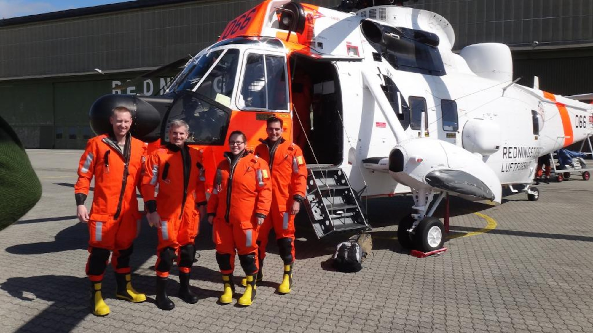 From left, Tech. Sgt. Tim Carlsrud, Maj. Kevin Catron, Staff Sgt. Jennifer Thaxton and Capt. Morgan Cowle pose in front of a Royal Norwegian Air Force Mk43B Sea King in their dry suits before being ferried out to an emergency life raft for a training exercise May 13, 2014, in the North Sea. The four Airmen are all from the 426th Air Base Squadron at Stavanger, Norway (Courtesy Photo)