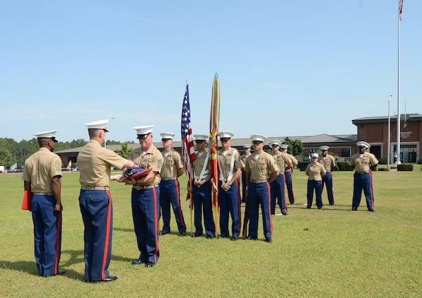 Sgt. Maj. Conrad Potts, outgoing sergeant major, Marine Corps Logistics Base Albany, receives an American flag flown in his honor over Coffman Hall from Col. Don Davis, commanding officer, MCLB Albany, during a retirement ceremony at Schmid Field, May 23.