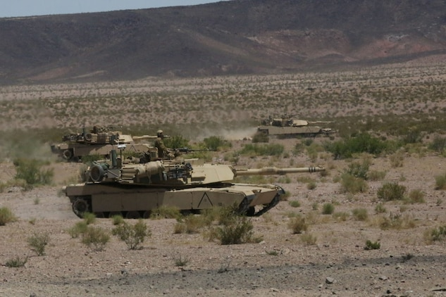 Marines with Alpha Company, 1st Tank Battalion, advance in formation on a mock enemy position in an M1A1 abrams main battle tank during Exercise Desert Scimitar aboard Marine Corps Air Ground Combat Center Twentynine Palms, Calif., May 11, 2014. The training gave the Marines the opportunity to refine and rehearse essential combat skills needed in a battlefield environment. Desert Scimitar is an annual exercise that includes elements from the I Marine Expeditionary Force. The exercise focused on conventional operations and provided realistic training that prepared Marines for overseas operations. (U.S. Marine Corps photo by Cpl. Christopher J. Moore/Released)