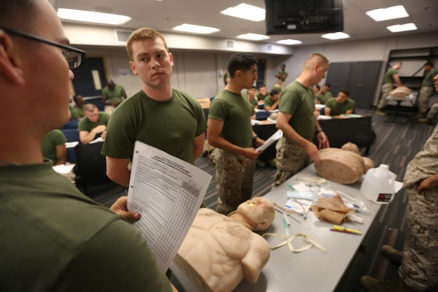 Students attending Field Medical Training Battalion quiz each other on procedures before a practical exam, May 23, 2014.  Marine Corps and Navy instructors from FMTB taught students the basics of hemorrhage control aboard Camp Pendleton, California.