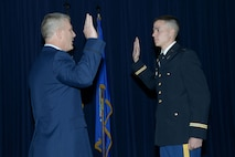 Col. Kyle 'Cowboy' Ingham administers the oath of office to 2nd Lt. Austin Ingham during ceremonies celebrating the colonel's retirement and his son's commissioning on May 20 at Joint Base-Randolph, Texas. (Air Force photo by Joel Martinez)
