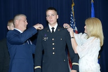 Col. Kyle 'Cowboy' Ingham and his wife Kira pin second lieutenant bars on their son Austin on May 20 at Joint Base-Randolph, Texas, as their son Houston looks on. (Air Force photo by Joel Martinez)