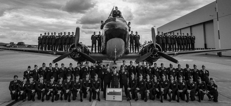 Members of the 37th Airlift Squadron gather for a group photo in front of a Douglas C-47 Skytrain, designated Whiskey 7, on Ramstein Air Base, Germany, May 29, 2014. The 37th AS recreated the historical photo to mimic a photo taken 70-years ago of the exact same aircraft with members of the 37th Troop Carrier Squadron. (U.S. Air Force illustration/Airman 1st Class Jordan Castelan)