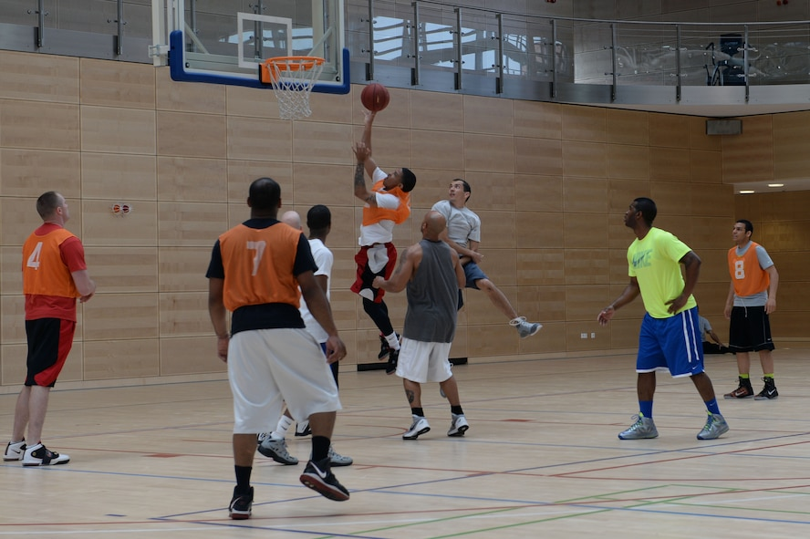 A member from the 606th Air Control Squadron team attempts to score during a wing sports day basketball tournament at Spangdahlem Air Base, Germany, May 29, 2014. Wing sports day kicked off with a wing-wide formation run. (U.S. Air Force photo by Senior Airman Alexis Siekert/Released)