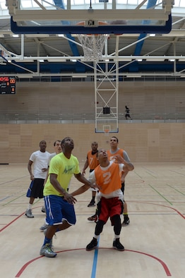 Team members from the 52nd Force Support Squadron and 606th Air Control Squadron wait for the ball to drop after a shot during a wing sports day basketball tournament at Spangdahlem Air Base, Germany, May 29, 2014. Airmen had the choice of playing basketball, kickball, dodge ball or golf and wing leadership participated in a tug of war at the end of the day. (U.S. Air Force photo by Senior Airman Alexis Siekert/Released)
