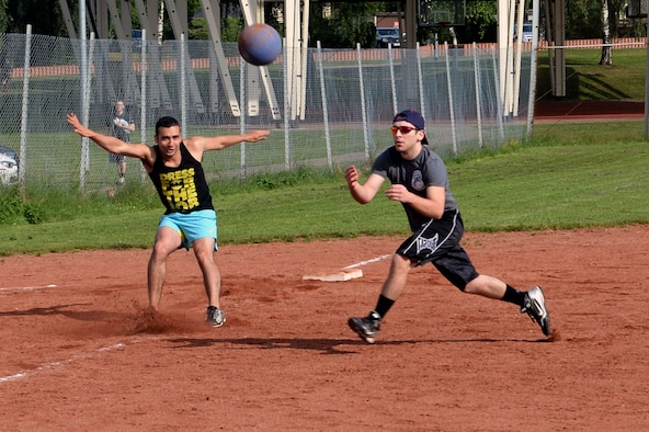 U.S. Air Force Senior Airman Gustavo Castillo, 52nd Fighter Wing Public Affairs photojournalist and Wing Staff Agency team member from Los Angeles, makes a hard stop off third base as a member of the 726th Air Mobility Squadron team makes a catch during a wing sports day kickball tournament at Spangdahlem Air Base, Germany, May 29, 2014. The WSA team won this match but was later eliminated in the tournament. (U.S. Air Force photo by Senior Airman Alexis Siekert/Released)