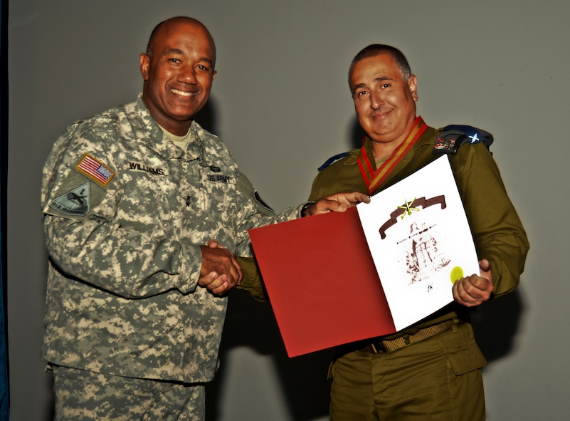 U.S. Army Maj. Gen. Darryl A. Williams, commander of U.S. European Command's Joint Defense Forces Israel, left, hands a certificate for the Order of Saint Barbara to Israeli Defense Force Brig. Gen. Shachar Shohat, the Air Defense Forces commander, right, during the closing ceremony of the bilateral Juniper Cobra 14 defense exercise at Hatzor Air Base, Israel, May 22, 2014. The Order of Saint Barbara is a U.S. military tradition bestowed upon persons who contribute to the field of artillery. JC14 training consists of computer-simulated exercises, providing training in defense, crisis resupply, foreign disaster response and foreign humanitarian assistance. (U.S. Air Force photo by Staff Sgt. Joe W. McFadden/Released)