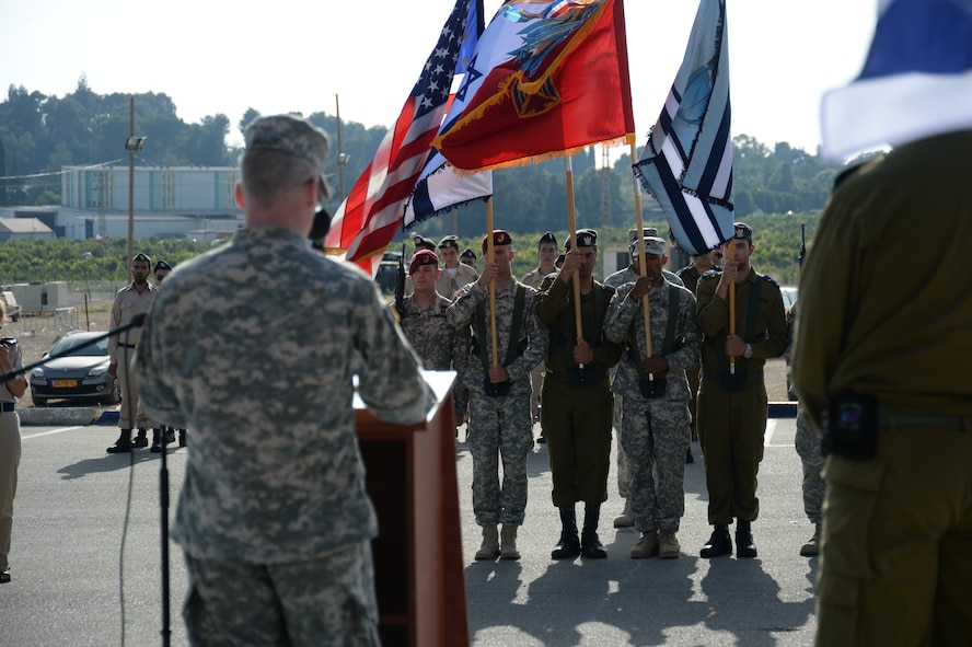 U.S. and Israeli color guard members bear their nations' and services' flags as U.S. Army Col. Greg Brady, commander of the 10th Army Air Missile Defense Command, left, speaks during the closing parade ceremony of the bilateral Juniper Cobra 14 defense exercise at Hatzor Air Base, Israel, May 22, 2014. JC14 is part of a long-standing agreement between U.S. European command and the Israeli Defense Force to hold bilateral training exercises on a regular basis in order to promote and sustain regional stability, and to ensure Israel's qualitative military edge. (U.S. Air Force photo by Staff Sgt. Joe W. McFadden/Released)