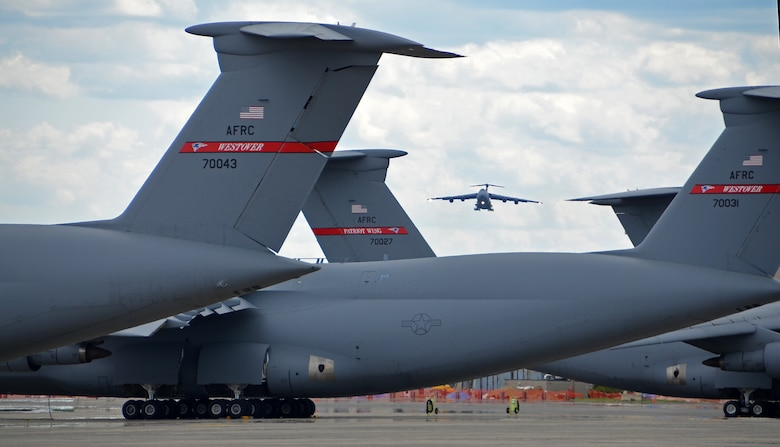 C-5 Galaxy tails on the flightline frame a C-5 on final approach May 19, 2014, to Westover Air Reserve Base, Mass. The C-5 has the ability to carry 36 standard pallets and 81 troops simultaneously. (US Air Force photo/Master Sgt. Andrew Biscoe)