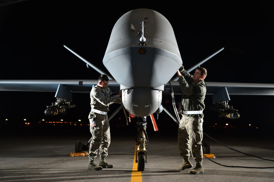 Airman 1st Class Steven (left) and Airman 1st Class Taylor prepare an MQ-9 Reaper for flight during exercise Combat Hammer, May 15, 2014, at Creech Air Force Base, Nev. Reaper crews flew a week-long mission, where they released the GBU-12 Paveway II and AGM-114 Hellfire munitions. Steven and Taylor are 432nd Aircraft Maintenance Squadron MQ-9 Reaper crew chiefs. (U.S. Air Force photo/Staff Sgt. Nadine Barclay)