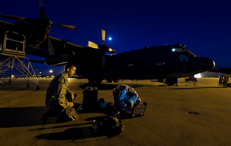 Senior Airman Christopher Hawkins and Airman 1st Class Eric Campbell, Aircraft Maintenance Unit aerospace propulsion journeymen, review technical orders before performing maintenance on an AC-130U Spooky Gunship at Hurlburt Field, Fla., May 16, 2014. The 4th AMU helps generate nearly 20 training mission flights each week. (U.S. Air Force photo/Senior Airman Christopher Callaway)