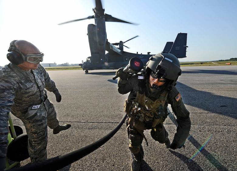 Senior Airman Johnathan Morgan, 1st Special Operations Logistics Readiness Squadron fuels journeyman, assists a CV-22 Osprey crew chief with a fuel hose at Hurlburt Field, Fla., May 20, 2014. The Osprey had to be refueled prior to its training mission. (U.S. Air Force photo/Staff Sgt. Jeff Andrejcik)