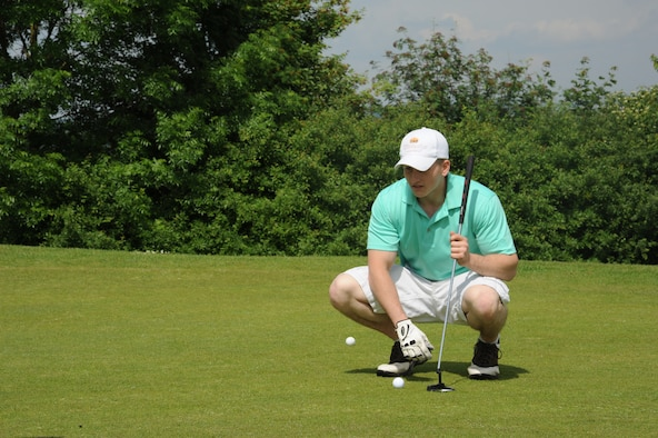 U.S. Air Force Senior Airman Michael Edwards, 606th Air Control Squadron radio frequency transmissions journeyman, aligns his putt during the wing sports day golf tournament May 29, 2014, at Spangdahlem Air Base, Germany. The 52nd Civil Engineer Squadron took home the overall title for wing sports day. (U.S. Air Force photo by Airman 1st Class Dylan Nuckolls/Released)