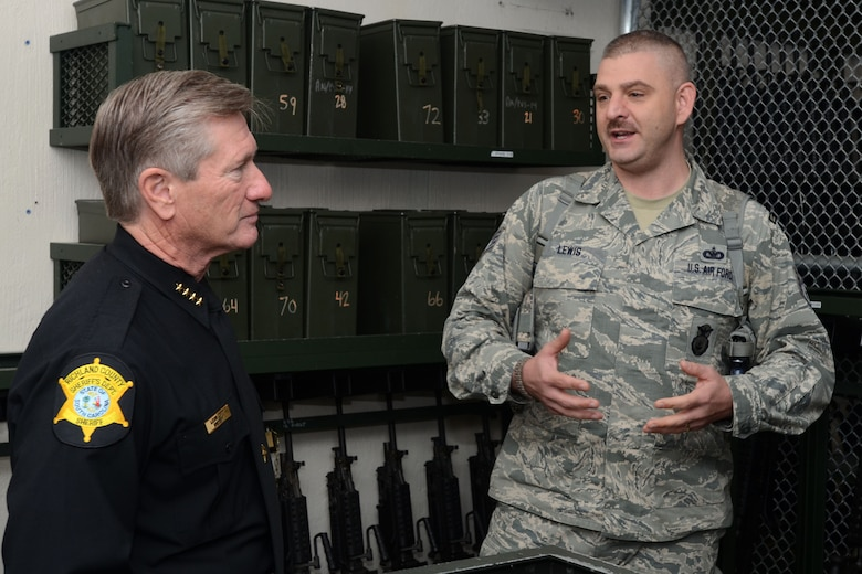 """U.S. Air Force Lt. Col. Paul Laymon, the Defense Force Commander for the 169th Security Forces Squadron, and Staff Sgt. Kenvyn Lewis, combat arms trainer for the 169th SFS, give Sheriff Leon Lott, from the Richland County Sheriff's Department, a tour of the unit's armory and weapons arsenal. Sheriff Lott received the title as """"Honorary Defense Force Commander"""" for the South Carolina Air National Guard's 169th Security Forces Squadron during a ceremony held at McEntire Joint National Guard Base, S.C., Nov. 1, 2014. This honor recognized Sheriff Lott as a community leader and supporter of the South Carolina Air National Guard to strengthen community relationships and share in team building training and experience. (U.S. Air National Guard photo by Senior Master Sgt. Edward Snyder/Released)"""
