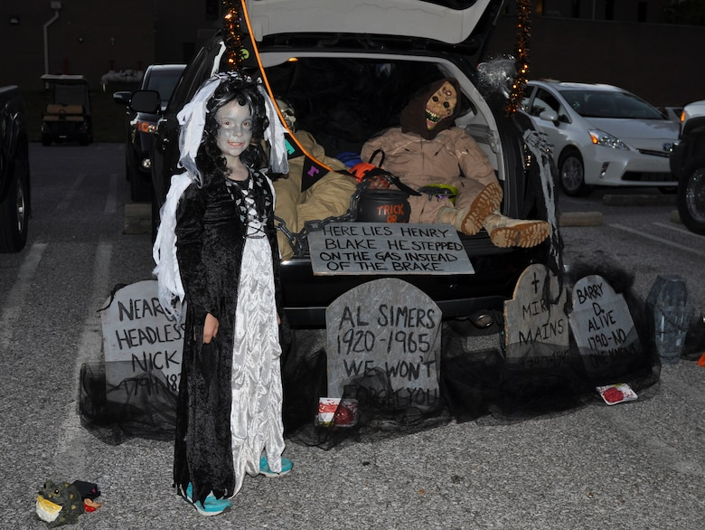 "A witch stands next her graveyard car during the 919th Special Operations Wing's ""Trunk of Treat"" event Oct. 30 at Duke Field, Fla.  More than 100 costumed kids and parents turned out to give and receive candy and goodies.  Trophies were also passed out to the best decorated vehicles.   (U.S. Air Force photo/Dan Neely)"
