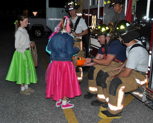 "The members of the 919th Special Operations Wing fire department pass out candy at the wing's ""Trunk of Treat"" Oct. 30 at Duke Field, Fla.  More than 100 costumed kids and parents turned out to give and receive candy and goodies.  Trophies were also passed out to the best decorated vehicles.   (U.S. Air Force photo/Dan Neely)"