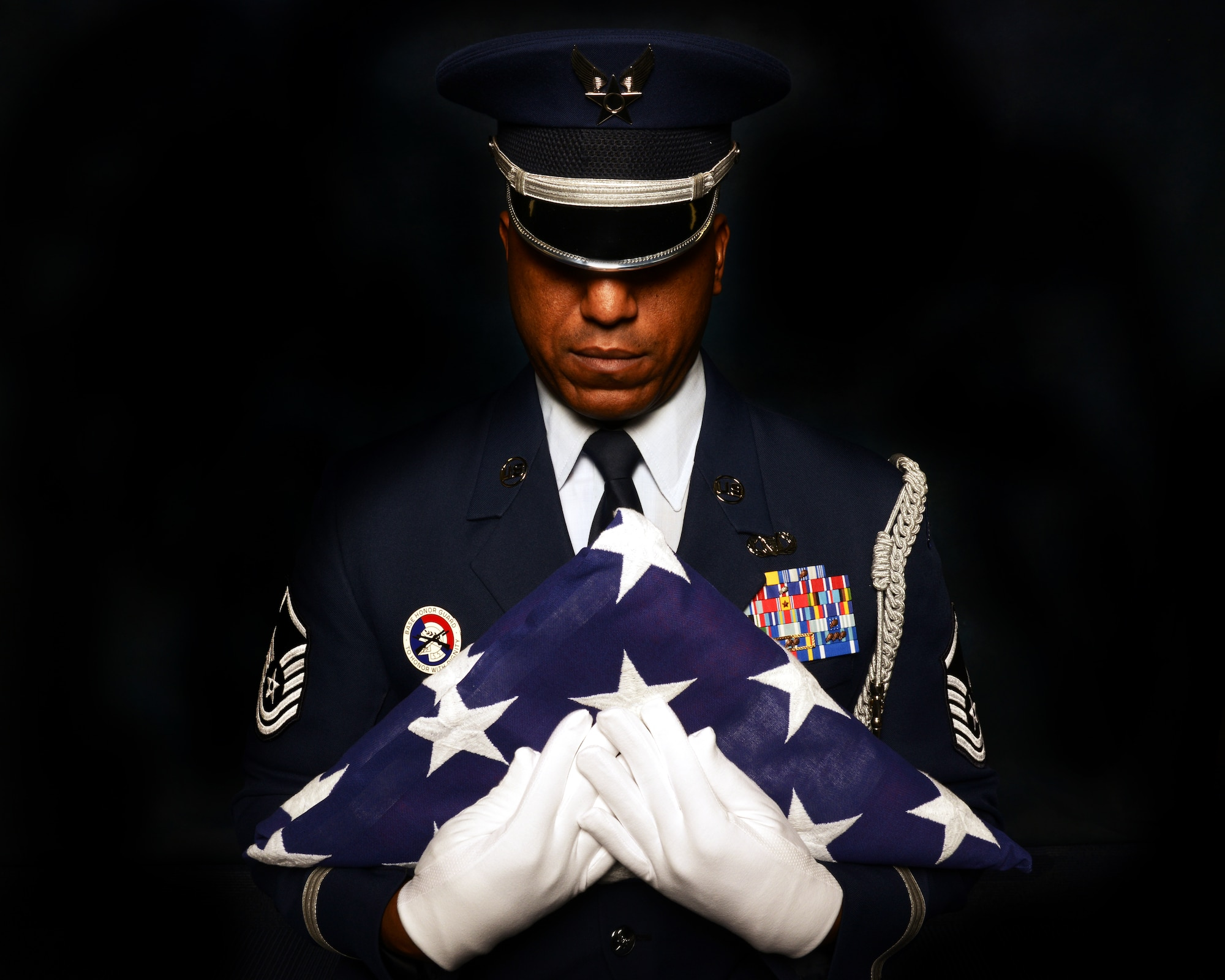 Master Sgt. Andre Moore clutches an American Flag to his chest during a studio portrait Oct. 28, 2014, at Aviano Air base, Italy. Moore served with the U.S. Air Force Honor Guard for more than four years and uses his knowledge to develop Airmen at the base honor guard level. Moor is the Aviano Base Honor Guard superintendent. (U.S. Air Force photo/Airman 1st Class Ryan Conroy)