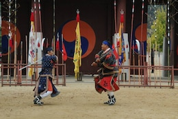 Two Korean guards perform a demonstration exhibiting their warrior skills at the Suwon Palace.