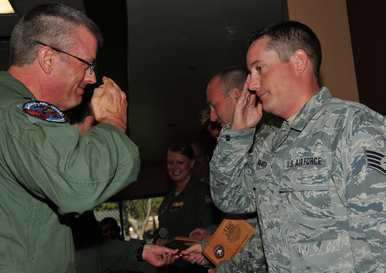 "(From Left) Lt. Col. Jim Gloss, 197th Air Refueling Squadron commander, presents Staff Sgt. Nick Savasta, 161st Maintenance Group crew chief, with the 161st Air Refueling Wing safety award for ""outstanding action"", Phoenix, Nov. 2, 2014. Savasta, along with crew chiefs Tech. Sgt. Bethany Skaritka and Staff Sgt. Chris Hostetler, prevented an in-flight emergency by noticing a hydraulic leak just as the aircraft was about to take off. ""The working relationship between Maintenance and Operations is integral to successful mission accomplishment, both during home station training and global operations,"" said Maj. Tami Demik, 161st Air Refueling Wing safety officer. ""Maintaining a positive and proactive safety culture, and employing accurate risk management techniques, allow the 161st Air Refueling Wing to deliver 100% mission effectiveness."" (U.S. Air National Guard Photo by Tech. Sgt. Courtney Enos/Released)"