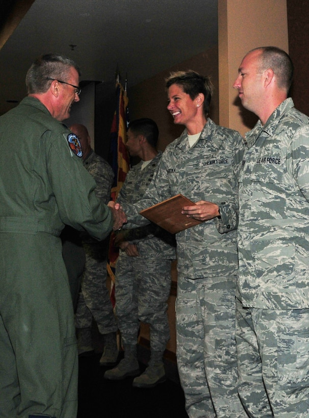 """(From Left) Lt. Col. Jim Gloss, 197th Air Refueling Squadron commander, presents 161st Maintenance Group crew chiefs Tech. Sgt. Bethany Skaritka and Staff Sgt. Chris Hostetler with the 161st Air Refueling Wing safety award for """"outstanding actions"""", Phoenix, Nov. 2, 2014. These crew chiefs, along with Staff Sgt. Nick Savasta, prevented an in-flight emergency by noticing a hydraulic leak just as the aircraft was about to take off. """"These types of recognitions go a long way with building a strong working relationship between Ops and Maintenance,"""" said Maj. Gilbert Besana, 161st Aircraft Maintenance Squadron commander. """"It also reminds our guys of how important their jobs are and reminds us all that 'if you see something, say something.'"""" (U.S. Air National Guard Photo by Tech. Sgt. Courtney Enos/Released)"""