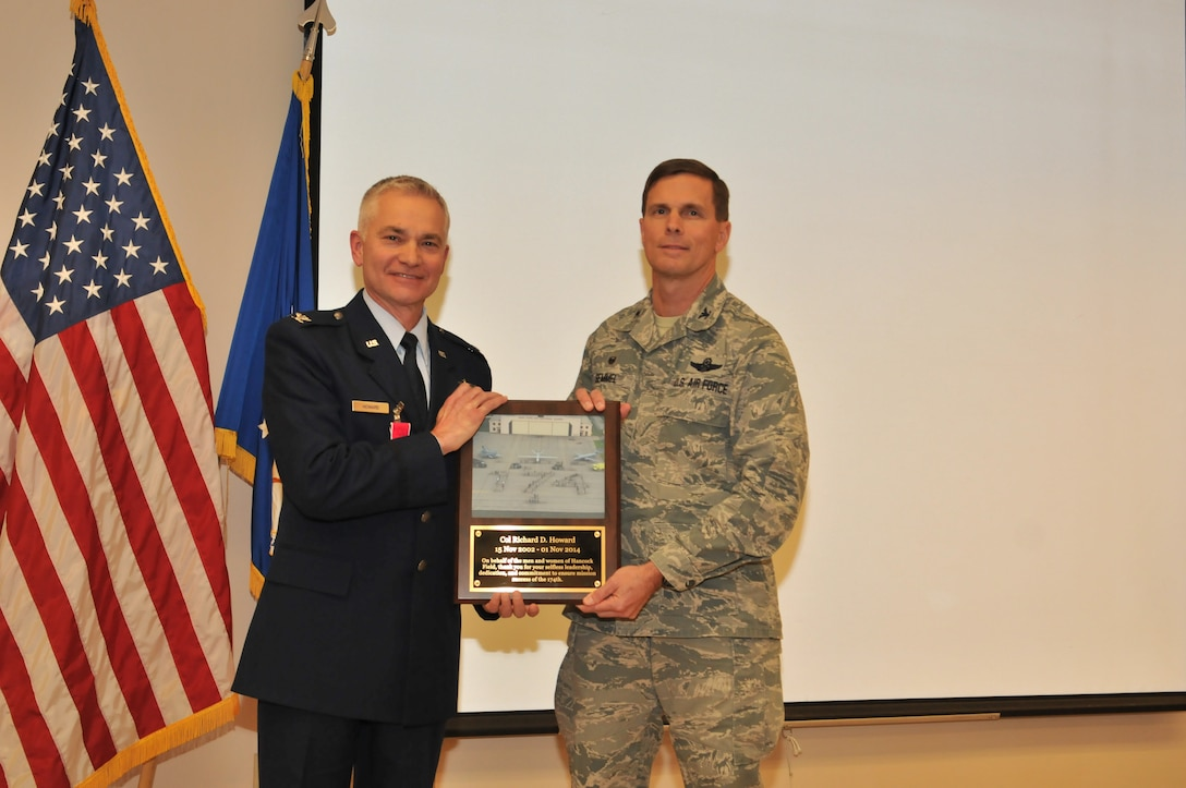 Col. Greg Semmel, Commander of the 174th Attack Wing presents Col. Richard D. Howard with a plaque in appreciation, recognition of service and dedication at his retirement ceremony. Howard served 34 years of service and retired on Nov. 1, 2014 at the 174th Attack Wing in Syracuse, NY. (New York Air National Guard Photo Tech. Sgt. Justin A. Huett/Released)