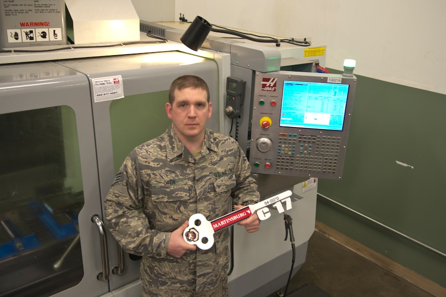 Staff Sgt. Johnathen Guzik holds a ceremonial key used for the arrival of the first C-17 aircraft to the 167th Airlift Wing. Guzik was instrumental in the creation of the key. The 167th Airlift Wing recently received it's first C-17 Globemaster III aircraft. The wing is converting from C-5's to C-17's. (Air National Guard photo by Tech. Sgt. Michael Dickson/released)