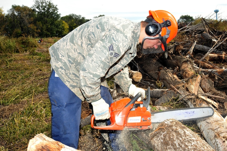 Senior Airman Cody Reece, 114th Civil Engineer Squadron HVAC technician, cuts a tree trunk to a manageable size during an operation in Delmont S.D. Oct. 4, 2014.  Nineteen Airmen from the 114th Civil Engineer Squadron deployed to Delmont to assist the city in removing large piles of debris left by recent summer storms.(National Guard photo by Tech. Sgt. Christopher Stewart/Released)