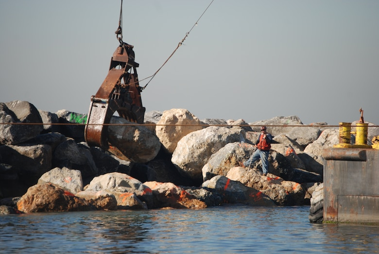 A spotter for Connolly Pacific helps the crane operator place a 10-ton rock along the Port of Long Beach Middle Breakwater. The work is being accomplished under a Corps of Engineers contract to repair damage the breakwater suffered in late August during heavy seas from Hurricane Marie.
