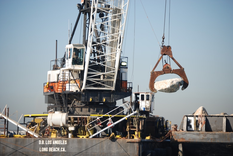 A Connolly Pacific crane operator moves a 9-ton rock into position along the Port of Long Beach Middle Breakwater. Repair work on the breakwater is being accomplished under a Corps of Engineers contract to repair damage suffered in late August during heavy seas from Hurricane Marie.