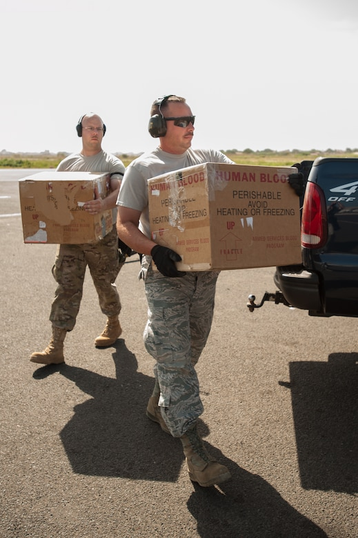 Airmen from the Kentucky Air National Guard's 123rd Contingency Response Group carry whole blood to a waiting U.S. Air Force C-130 Hercules at Léopold Sédar Senghor International Airport in Dakar, Senegal, Oct. 22, 2014. The blood is being sent to Liberia to support U.S. troops deployed for Operation United Assistance, the U.S. Agency for International Development-led, whole-of-government effort to respond to the Ebola outbreak in West Africa. (U.S. Air National Guard photo by Maj. Dale Greer)