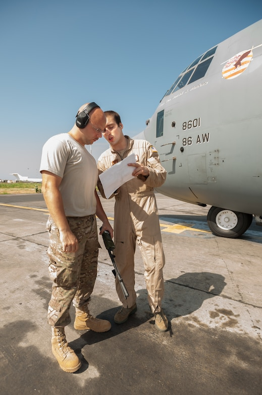 U.S. Air Force Tech. Sgt. Jarrod Blanford, an aerial porter from the Kentucky Air National Guard's 123rd Contingency Response Group (left), reviews a cargo manifest with U.S. Air Force Airman 1st Class Evan Kuehl, a loadmaster from the 86th Airlift Wing, prior to the departure of a C-130 Hercules from Léopold Sédar Senghor International Airport in Dakar, Senegal, Oct. 22, 2014. The flight is bound for Liberia, carrying whole blood and U.S. Army Soldiers supporting Operation United Assistance, the U.S. Agency for International Development-led, whole-of-government effort to respond to the Ebola outbreak in West Africa. (U.S. Air National Guard photo by Maj. Dale Greer)