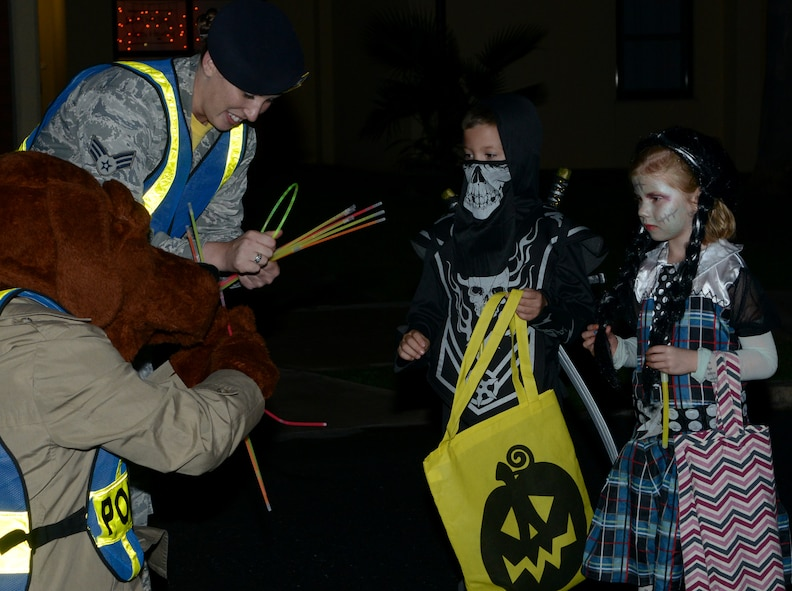 Members of the 39th Security Forces Squadron, along with McGruff the Crime Dog, pass out glow sticks and candy during Pumpkin Patrol Oct. 31, 2014, at Incirlik Air Base, Turkey. Pumpkin Patrol is an event hosted by the 39th SFS, where defenders patrol through base housing and gave out candy and glow sticks on Halloween night. (U.S. Air Force photo by Staff Sgt. Caleb Pierce/Released)