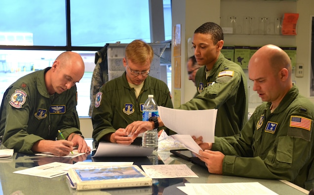 Pilot and mission commander U.S. Air Force Maj. Troy Bockius, combat systems officer (CSO) Maj. Roy Shoppert, pilot Lt. Col. J.D. Davis (background), pilot 1st Lt. Chris Farrell and CSO 1st Lt. Alex Sutherland, all from the 142nd Airlift Squadron, 166th Airlift Wing, Delaware Air National Guard at a mission planning meeting for a two-ship C-130H formation and airdrop mission on Oct. 22, 2014 at the New Castle ANG Base, Del. (U.S. Air National Guard photo by Tech. Sgt. Benjamin Matwey)
