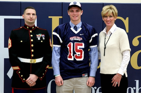 WYNDMOOR, Pa. - Gunnery Sgt. Luke Penniman, staff noncommissioned officer with Recruiting Substation Tun Tavern, Kyle Shurmur, star quarterback from La Salle College High School and his mother, Jennifer, pose for a photo after Kyle was presented his official Semper Fidelis All-American Bowl jersey, Oct. 27. Kyle, with a commitment to Vanderbilt, will be playing with dozens of other outstanding high school football players from across the country in the SFAAB on Jan. 4th at the StubHub Center in Carson, Calif.