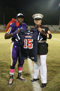 Staff Sgt. Travis Godley, canvassing recruiter, Marine Corps Recruiting Substation Lexington presents Jonathon Sutton, senior, Swansea High School with his Semper Fidelis All-American Bowl jersey during half-time of his last home football game at Swansea High School on Oct. 31, 2014.