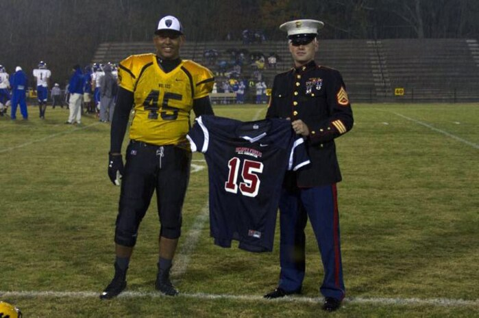 Staff Sgt. Louis Damico, canvassing recruiter, Marine Corps Recruiting Substation Gastonia presents Darian Roseboro, senior, Lincolnton High School with his Semper-Fidelis All-American Bowl jersey before kick-off of his last home football game at Lincolnton High School on Oct. 31, 2014.