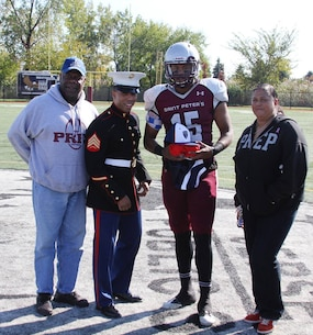 Sgt. Sergio Castro recognizes St. Peter's Preparatory School senior football player Jordan Fox prior to the game vs Union City for being selected to play in the the 2015 Semper Fidelis All-American Bowl game, Oct. 25, 2014. Fox is accompanied by his father Daniel (left) and his mother Donnette (right). Fox was selected for his athletic ability, academic prowess, and commitment to the community. The game features 100 of the best student-athletes across the country and will be played at The StubHub Center in Carson, Calif., on Jan. 4, 2015. It will be aired on Fox Sports 1 at 9 p.m. EST. For more information go to semperfidelisfootball.com.