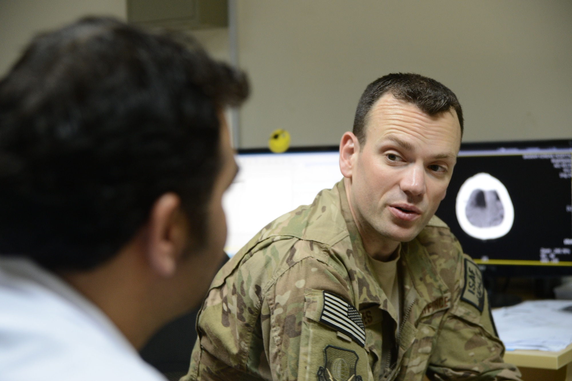 Maj. Jonathan Forbes consults with Dr. Ahmed, an Afghan doctor with the Korean Humanitarian hospital, Oct. 22, 2014, at Bagram Airfield, Afghanistan. Forbes is a neurosurgeon assigned to the 455th Expeditionary Medical Group and removed a tumor from the man's brain 12 days earlier. (U.S. Air Force photo/Master Sgt. Cohen A. Young)