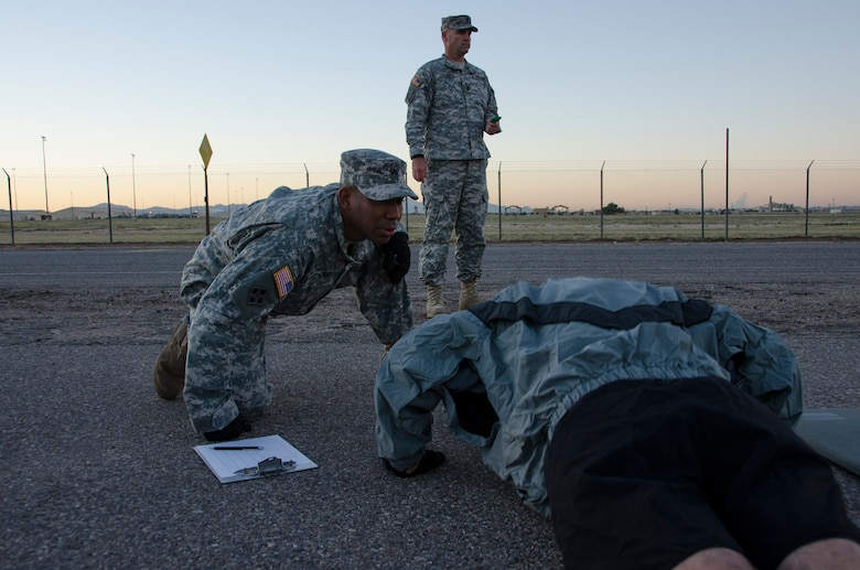Sgt. Kelly Greenidge, 1st Battlefield Coordination Detachment Fire Support NCO, observes as a member begins the push-up portion of the Army physical fitness test at Davis-Monthan AFB, Ariz., Nov. 4, 2014. During this portion Greenidge is ensuring the member breaks a 90 degree angle, as well as telling them their current count. (U.S. Air Force photo by Staff Sgt. Adam Grant/Released)