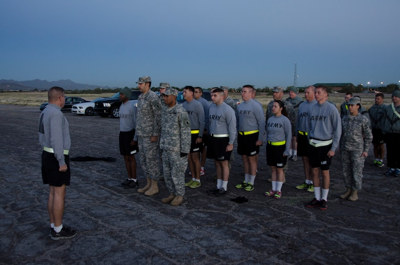 Sgt. Maj. Kazimier Kazimierowski, 1st Battlefield Coordination Detachment Sergeant Major, assesses soldiers during a formation before preparing to take the Army physical fitness test at Davis-Monthan AFB, Ariz, Nov. 4, 2014. The Army physical fitness test is broken down in to three events, push-ups, sit-ups and a two mile run. (U.S. Air Force photo by Staff Sgt. Adam Grant/Released)
