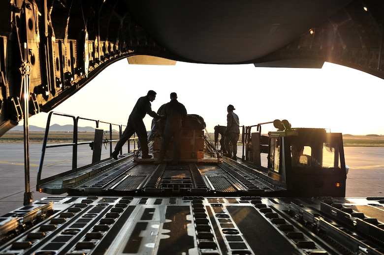 ALTUS AIR FORCE BASE, Okla. – Airmen from the 97th Logistics Readiness Squadron air delivery flight and the 58th Airlift Squadron prepare to load a cargo pallet onto a U.S. Air Force C-17 Globemaster III cargo aircraft for a training mission Oct. 30, 2014. The cargo pallet is made up of lumber and simulates the relative actual weight of supply airdrops used in global contingency and humanitarian operations. (U.S. Air Force Photo by Senior Airman Dillon Davis/Released)