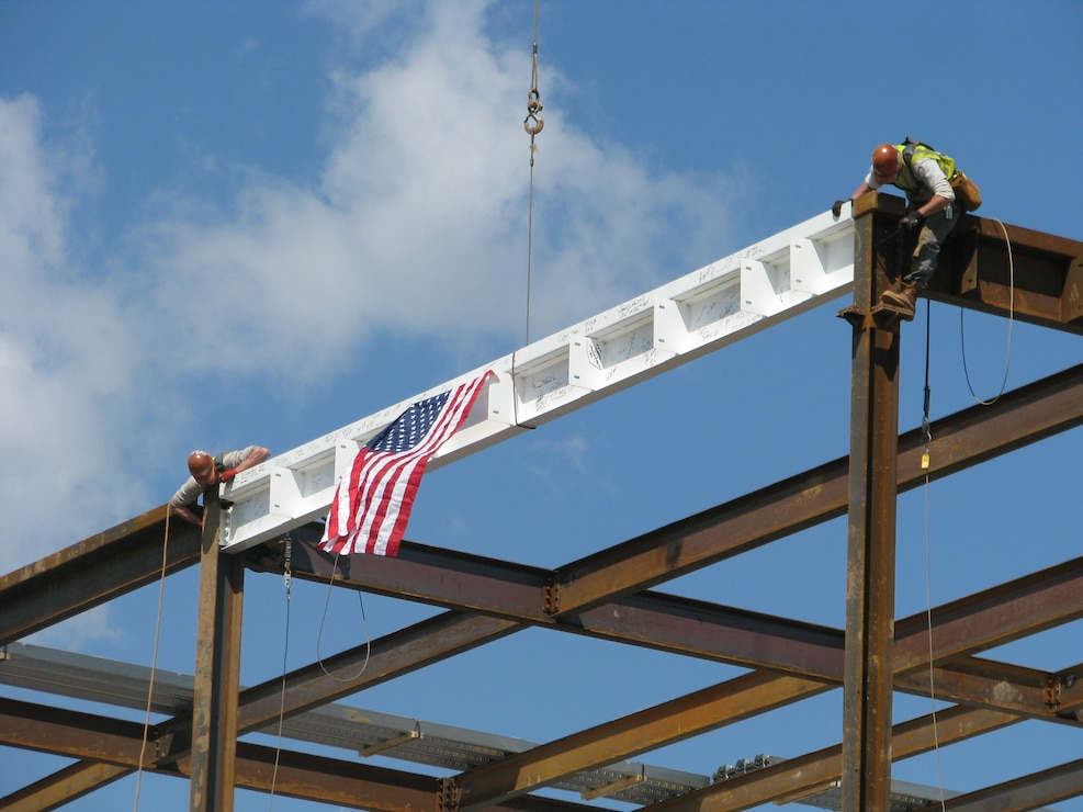 Construction workers proudly hang the American flag on the final piece of structural steel on the new DLA headquarters building at Defense Distribution Depot Susquehanna on Apr. 9.