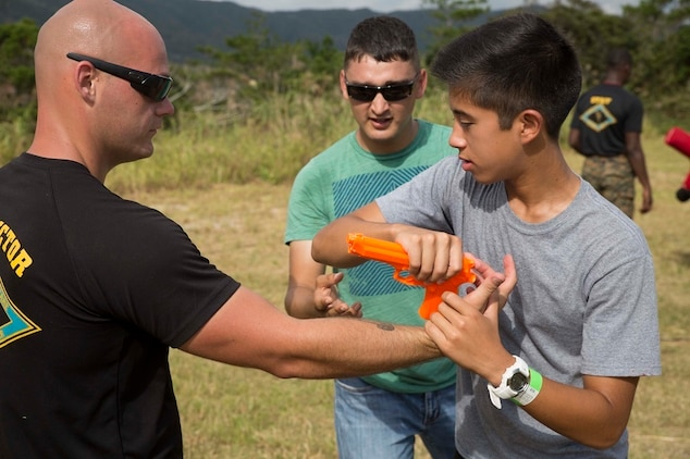Donald W. Christensen, right, learns to disarm a weapon from Cpl. Ryan T. Starr Oct. 25 during Junglefest 2014 at the Jungle Warfare Training Center on Okinawa, Japan. The festival allowed Okinawa community members and U.S. service members to see and experience some of the military training techniques that the instructors at the JWTC teach during the jungle survival training course. Christensen is a student  and child of an active duty service member on Okinawa. Starr, from Waldron, Arkansas, is an instructor at the Jungle Warfare Training Center.
