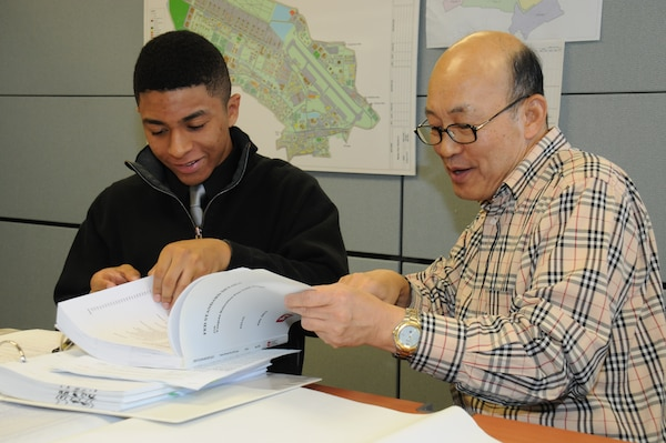 Seoul American High School senior Warren Nieto (left) learns about mechanical engineer design drawings from Eugene Min, chief of the tech review section at the district compound Nov. 5.