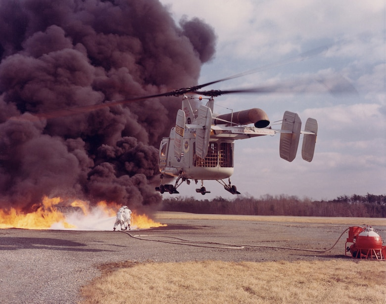 HH-43 crew practicing Local Base Rescue/Firefighting. Downwash air from the rotors opened a path for rescuers to spray foam from the red and white fire suppression kit in the lower right. (U.S. Air Force photo)